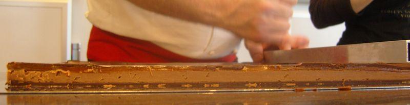 Caramel praliné montée de sa ganache earl grey aux fleurs bleues surmontés d'un glacage au chocolat en cours